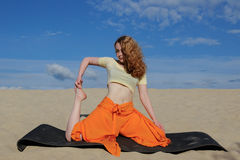Young redhead woman practicing yoga on the beach Stock Photo