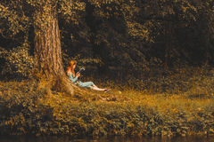 Young redhead woman reading book in autumn park. Young woman sitting on the grass and reading a book in the autumn park Stock Photo
