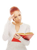 A young redhead woman reading a red book Royalty Free Stock Photos