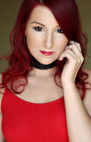 The young redhead woman in red top with black ribbon on the neck Stock Image