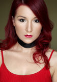 The young redhead woman in red top with black ribbon on the neck Royalty Free Stock Images