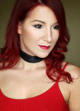 The young redhead woman in red top with black ribbon on the neck Royalty Free Stock Photos