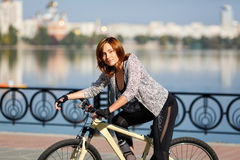 Young redhead woman riding a bike on embankment. Active people outdoors. Sport lifestyle. Stock Photography