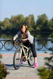 Young redhead woman riding a bike on embankment. Active people outdoors. Sport lifestyle. Stock Images