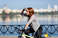Young redhead woman riding a bike on embankment. Active people outdoors. Sport lifestyle. Royalty Free Stock Image