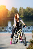 Young redhead woman riding a bike on embankment. Active people outdoors. Sport lifestyle. Royalty Free Stock Photography