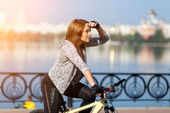 Young redhead woman riding a bike on embankment. Active people outdoors. Sport lifestyle. Stock Image