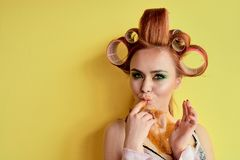Young redhead woman with shugaring paste on her hands, face, body and chest. Young redhead woman with hair curlers. Advertising concept of shugaring paste stock images