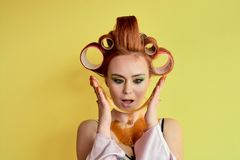 Young redhead woman with shugaring paste on her hands, face, body and chest. Young redhead woman with hair curlers. Advertising concept of shugaring paste royalty free stock photography