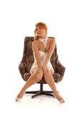 A young redhead woman sitting on an armchair Stock Image
