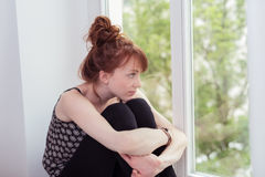 Young redhead woman sitting daydreaming Stock Photos