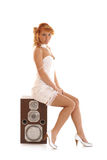 A young redhead woman sitting on a large speaker Stock Photos