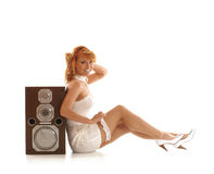 A young redhead woman sitting near a large speaker Stock Image