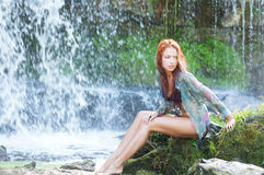 A young redhead woman sitting near the waterfall Stock Photo