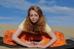 Young redhead woman sitting in purna titli yoga pose on the beac Stock Photos