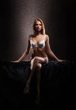 A young redhead woman sitting in white lingerie Royalty Free Stock Photo