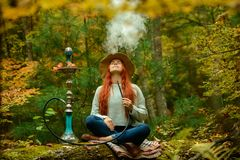 Young Redhead Woman Smoking Hookah In Forest Royalty Free Stock Images