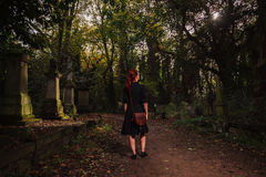 Young redhead woman standing in cemetery Stock Photos