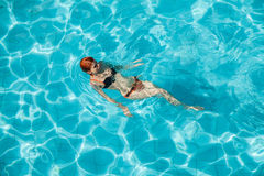 Young redhead woman in swimming pool Royalty Free Stock Photos