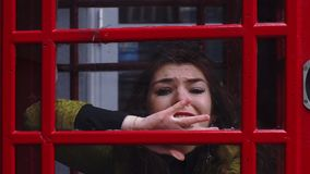 Young redhead woman trying to get out of the telephone booth stock video footage