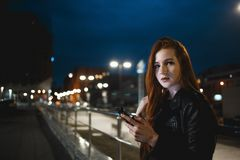 Young redhead woman using mobile phone on night street.  royalty free stock photos