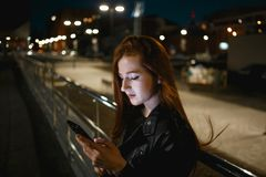 Young redhead woman using mobile phone on night street.  royalty free stock image
