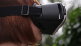 Young redhead woman using VR-helmet for smart phones. Augmented reality stock video