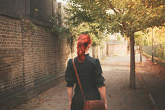 Young redhead woman walking in alley Stock Photos