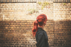 Young redhead woman walking in alley Royalty Free Stock Image
