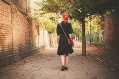 Young redhead woman walking in alley Stock Photography