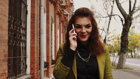 Young redhead woman walking in a street talking on the phone stock footage