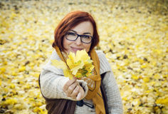 Young redhead woman with yellow autumn leaves Stock Photography