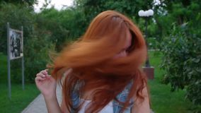 Young redhead women shaking her head in city park stock video