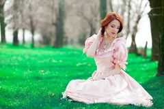 Young redheadd girl in victorian style dress. Portrait of a young redheadd girl in victorian style dress sitting on grass in springtime stock images