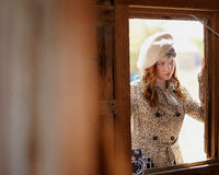 Young redheaded girl. Standing in a window Stock Photos
