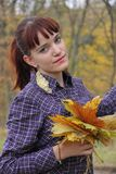 Young redheaded girl with a bouquet of autumn leaves Royalty Free Stock Photography