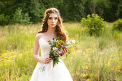Young redheaded girl walk in the park with bouquet of flowers Royalty Free Stock Photos