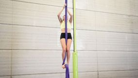 Young redheaded woman doing aerial gymnastic acrobatics with acrobatic fabrics inside a gym. stock video