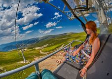 Young redheaded woman enjoying a ride on an open-air ropeway. In scenic mountains Stock Image