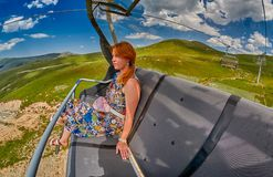 Young redheaded woman enjoying a ride on an open-air ropeway. In scenic mountains Stock Images