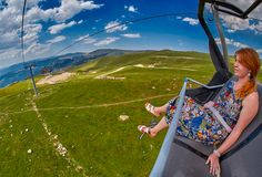 Young redheaded woman enjoying a ride on an open-air ropeway. In scenic mountains Stock Photos
