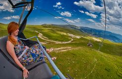 Young redheaded woman enjoying a ride on an open-air ropeway. In scenic mountains Stock Photo