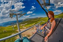 Young redheaded woman enjoying a ride on an open-air ropeway. In scenic mountains Royalty Free Stock Image