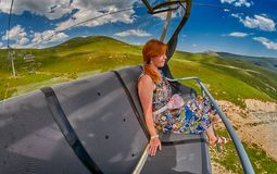 Young redheaded woman enjoying a ride on an open-air ropeway. In scenic mountains Stock Photography