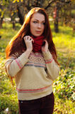 Young redheaded woman with long straight hair in the apple garden. Making a braid stock image