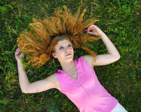 Young redheaded woman lying on the grass Royalty Free Stock Photography