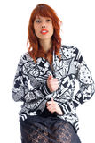 Young redheaded woman poses for the photo. Wearing black and whi. A redheaded girl sits in a comfortable chair and wears a black and white floral pattern jacket Stock Images