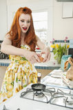 Young redheaded woman preparing omelet in kitchen Stock Image