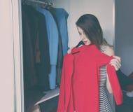 Young rednead girl choosing a clothes Stock Photos