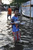 A young refugee boy is bringing food in a flooded street of Bangkok, Thailand, on 31 October 2011 royalty free stock photos